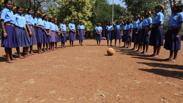 WS of a group of schoolgirls in school uniforms lined up and divided in two teams on a football field at a school in the village Satia a small...