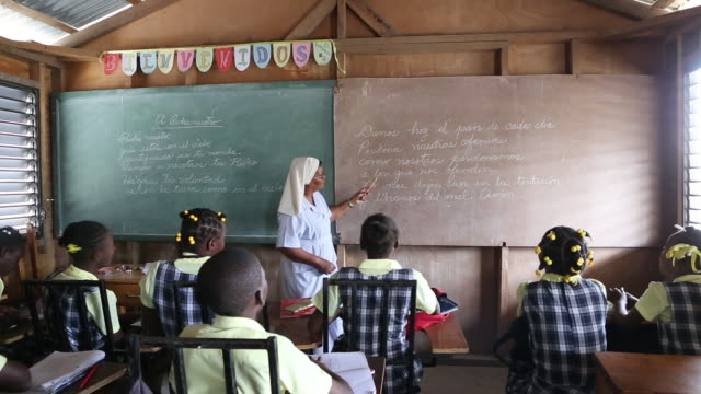 of a group of students during class which is held by a nun who is standing in front of a blackboard and reading aloud in port-au-prince, haiti. - nun stock videos & royalty-free footage