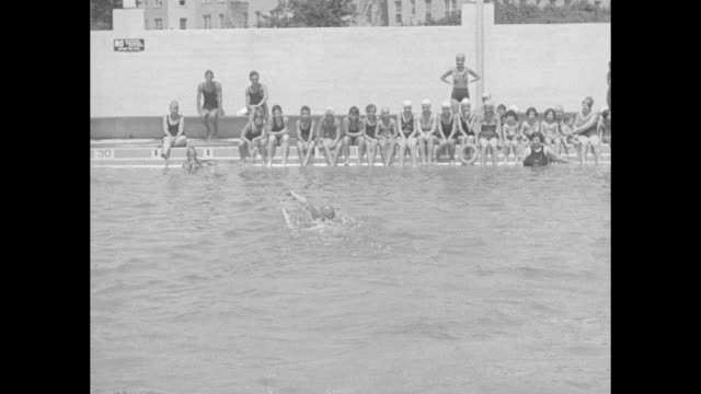 vídeos y material grabado en eventos de stock de vs a group of young people is seen across a swimming pool with a unidentified woman who repeatedly swims back and forth / note exact year not known... - gorro de baño