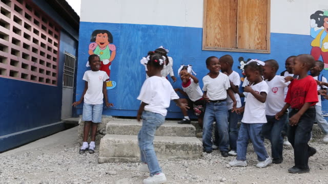 ws of a group of young schoolgirls and schoolboys that are playing on a schoolyard at nursery school in portauprince haiti in front of blue wall with... - afro caribbean ethnicity stock videos and b-roll footage