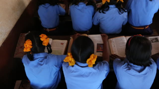 TU of a group of young schoolgirls who are reading a book at their desk during class in a school in the village Satia a small settlement 300...