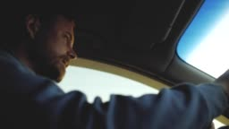 a guy with a beard with beautiful eyes is driving a car. sun rays in the window