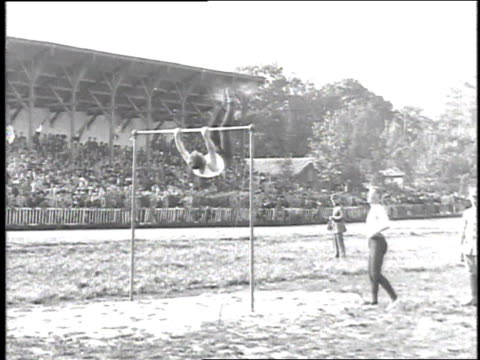 1918 ws a gymnast performing on the high bar, another man spotting him on the ground / france - 1918 stock videos and b-roll footage