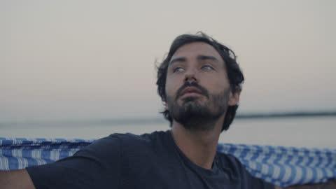 vídeos y material grabado en eventos de stock de cu of a handsome depressed man looking out at the ocean wrapped in a blanket - hombres jóvenes