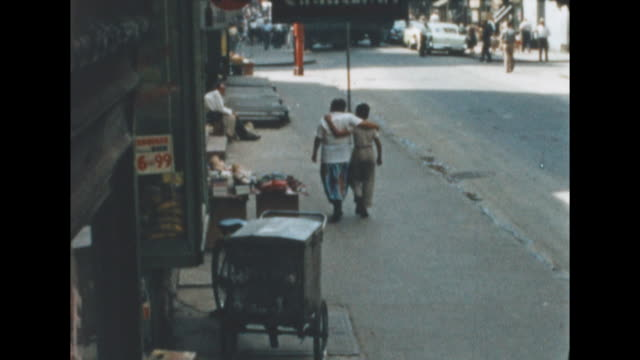 vídeos de stock, filmes e b-roll de ws of a hardware store in new york's lower east side man pushing a food cart / hot dog stand walks by women's bridal / wedding dresses are in the... - de braços dados
