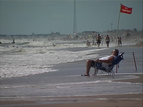 ls of a heavy man sitting in a lawn chair at the beach as waves come up the sand to his feet in point pleasant new jersey while people in the... - ocean avenue stock videos & royalty-free footage