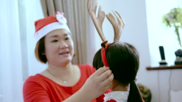 a helping hand of thai mother to wear christmas head-wear for her daughter - headwear stock videos & royalty-free footage