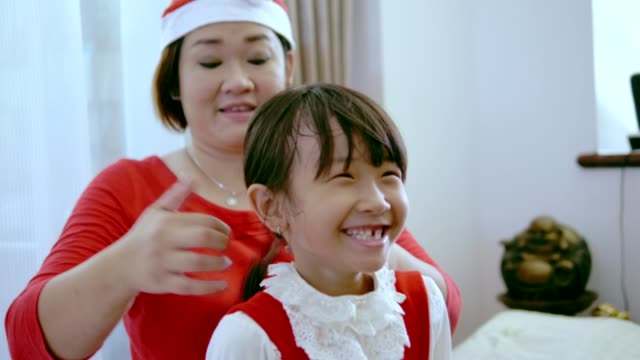 a helping hand of Thai mother to wear Christmas head-wear for her daughter