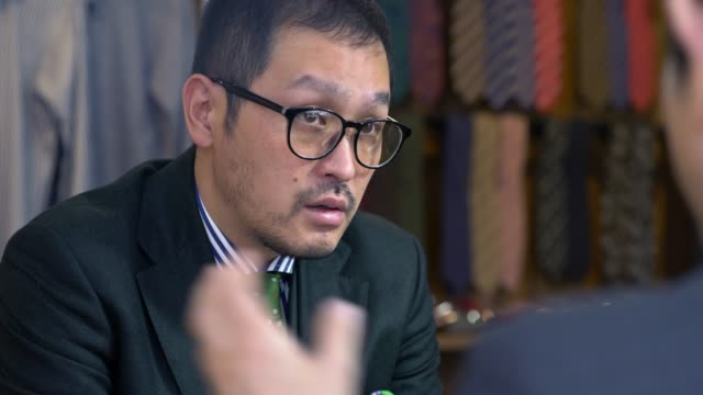 stockvideo's en b-roll-footage met cu van een high-end kleermaker in gesprek met een klant - kwaliteit