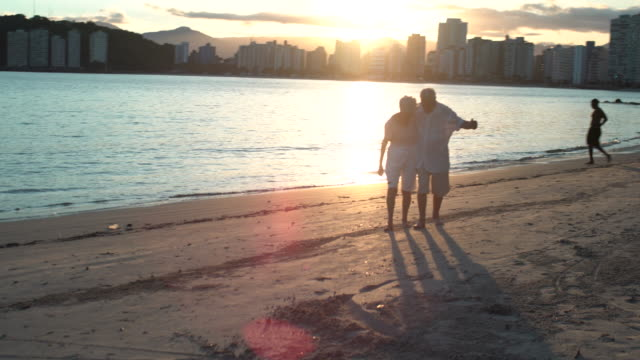 vídeos de stock, filmes e b-roll de ws of a hugging elderly couple walking towards the camera with the old man singing , dancing and having fun at the sunset on the beach. - homens idosos