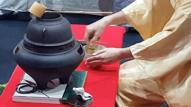 vídeos y material grabado en eventos de stock de una mujer japonesa muestra la ceremonia del té durante una manifestación pública - sado
