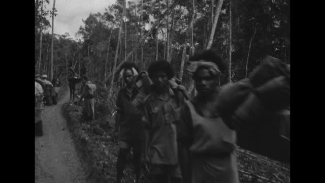 VS a jeep carrying Gen Douglas MacArthur drives though a village in the New Guinean jungle and passes natives standing alongside road / the vehicles...