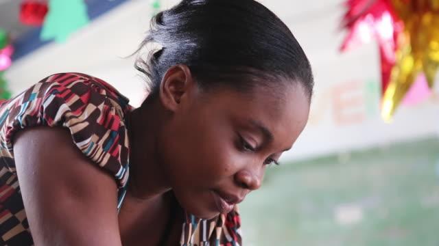 of a kindergarten teacher who is probably helping a schoolboy during class in a nursery school in port-au-prince, haiti. - preschool stock videos & royalty-free footage