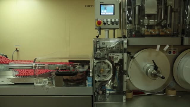 WS a labeling machine in the labeling unit MS labeled vaccines exit a labeling machine CS labeled vials exit a machine from a conveyor CS red caps of...