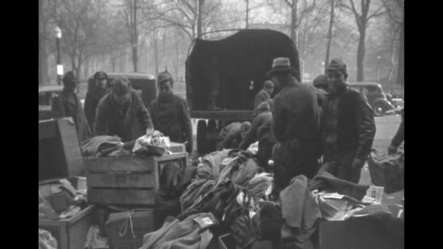 vs a large disorganized pile of clothing with civilian conservation corps men and boys loading the items onto trucks one overloads a trucks with... - civilian conservation corps stock-videos und b-roll-filmmaterial