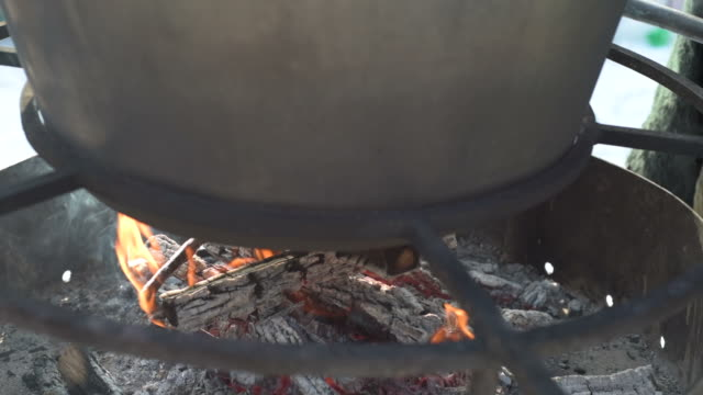 a large pot on the fire with mulled wine