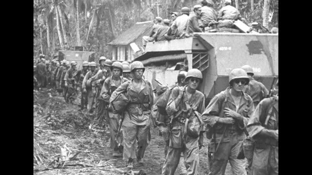 vídeos y material grabado en eventos de stock de vs a line of american troops trudge through a filipino village as a continuous track vehicle drives past with men on top / jeeps bump through a deep... - infinito
