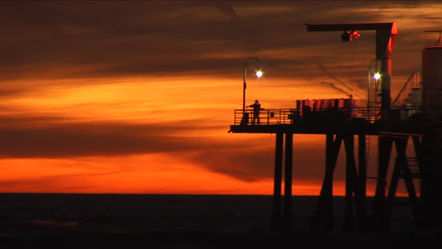 a lone fisherman casts his line from the santa monica pier after the sunset during magic hour of light - santa monica pier stock videos & royalty-free footage