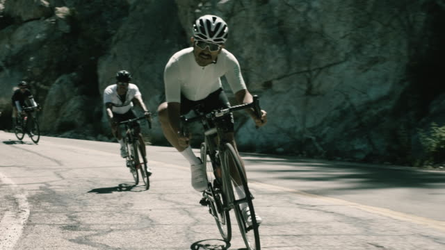a male cyclist leads a multi-ethnic group of male riders on a high-speed descent of a winding mountain road. - mountain ridge stock videos & royalty-free footage