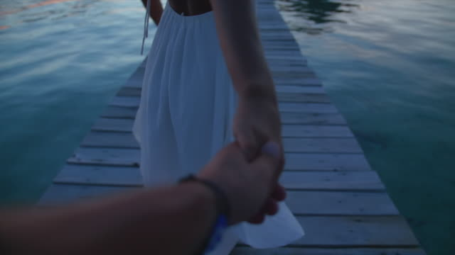 pov of a man and woman couple holding hands, traveling at night tropical island in overwater bungalow hotel resort. - パレオ点の映像素材/bロール