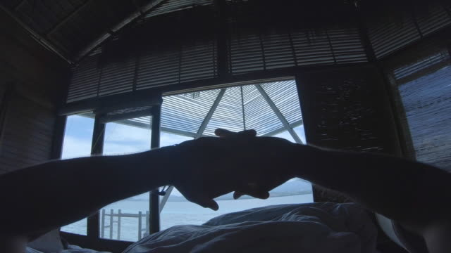 pov of a man and woman couple sleeping in bed and waking up at a tropical island in overwater bungalow hotel resort in a lagoon. - wake water stock videos & royalty-free footage
