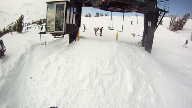 POV of a man and woman snowboarding off a chair lift at a mountain resort in winter. - Slow Motion - Model Released - HD