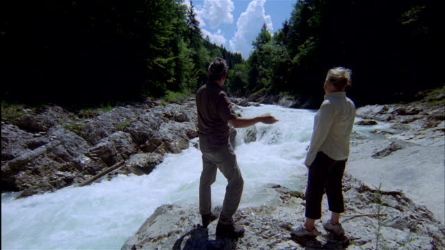 wide shot a man and woman stand on a rock near rapids of rissbach river in tyrol, austria. - 手をかざす点の映像素材/bロール
