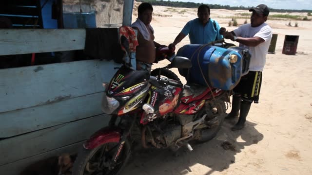 ms a man attaching plastic petrol canisters to a motorbike in an area strongly affected by illegal gold mining the region of madre de dios in... - bombola video stock e b–roll