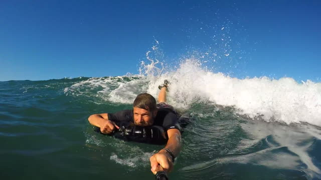 pov of a man bodysurfing on an inflatable surfmat. - slow motion - camcorder stock videos & royalty-free footage