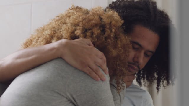 cu of a man consoling his girlfriend after she shows him a negative pregnancy test result - relationship difficulties stock videos & royalty-free footage