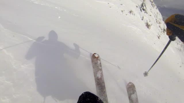 POV of a man downhill skiing.