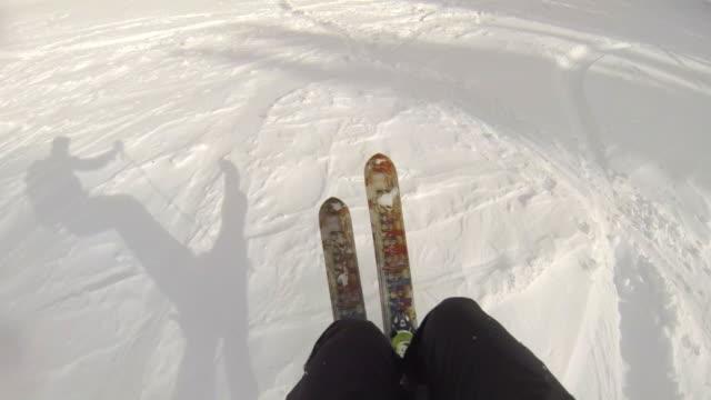 pov of a man downhill skiing. - cappotto invernale video stock e b–roll