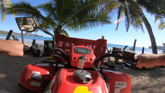 pov of a man driving an atv quad motorized vehicle to a scenic beach. - quadbike stock videos & royalty-free footage