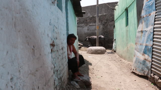 MS of a man is sitting at a door outside a shack in a narrow alley in a poor village on March 28 2013 in Bijapur India A cow can be seen in the...