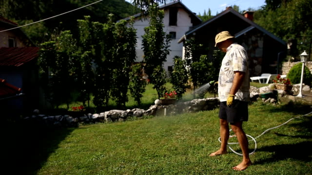 en man är vattning en gräsmatta nära huset - vattna bildbanksvideor och videomaterial från bakom kulisserna