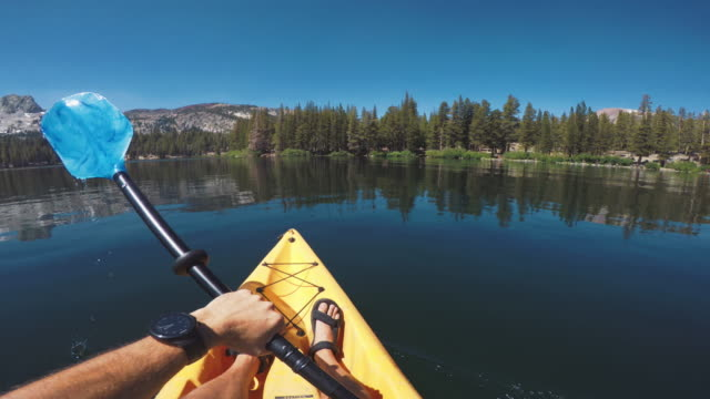 pov of a man kayaking in a calm lake - canoeing stock videos and b-roll footage