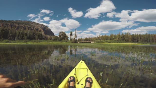 pov of a man kayaking in a calm lake - mammoth lakes video stock e b–roll