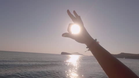 pov of a man making an ok sign symbol with his hand to the sun on a sailboat anchored in greece. - slow motion - ok sign stock videos & royalty-free footage