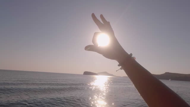 pov of a man making an ok sign symbol with his hand to the sun on a sailboat anchored in greece. - slow motion - motorboot stock-videos und b-roll-filmmaterial