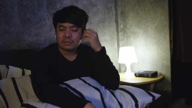 a man on a bed uses smartphone and listen to music - bedtime stock videos & royalty-free footage