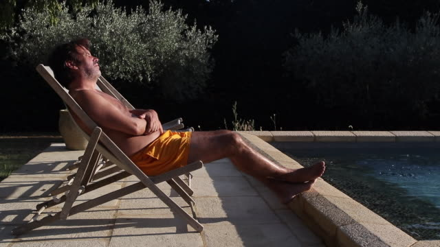 vidéos et rushes de a man on a deck chair by the pool - chaise