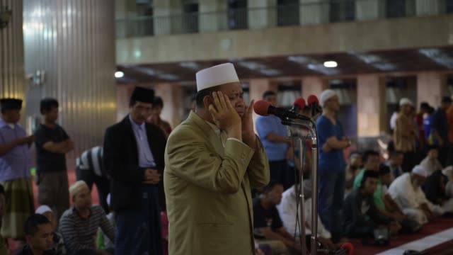 MS a man performs Adzan a prayer call at Istiqlal Mosque