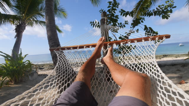 pov of a man relaxing in a hammock on a tropical island. - slow motion - riposarsi video stock e b–roll