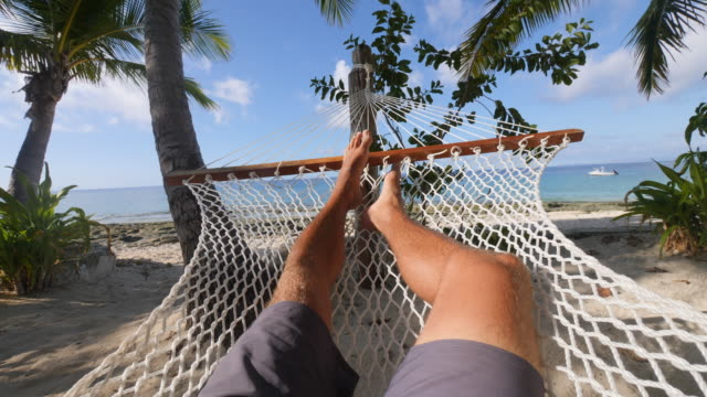 pov of a man relaxing in a hammock on a tropical island. - napping stock-videos und b-roll-filmmaterial