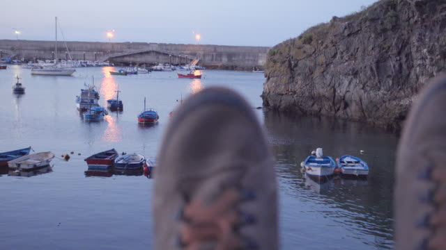 vídeos de stock e filmes b-roll de 4k | pov of a man resting at a sea fishing port at dusk. defocus mountain boots on the foreground and fishing boats on focus on the background. - só homens maduros