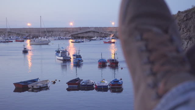 4K | POV of a man resting at a sea fishing port at dusk. Defocus mountain boots on the foreground and fishing boats on focus on the background.