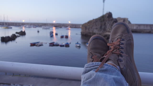 4K | POV of a man resting at a sea fishing port at dusk. Mountain boots appear on the foreground with crossed leg and fishing boats defocus on the background.