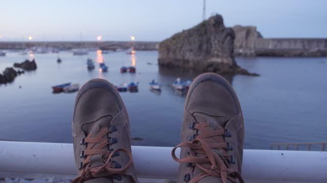 4k | pov of a man resting at a sea fishing port at dusk. mountain boots on the foreground and fishing boats defocus on the background. - endast en medelålders man bildbanksvideor och videomaterial från bakom kulisserna