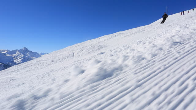 POV of a man skiing in the mountains in fresh powder snow.