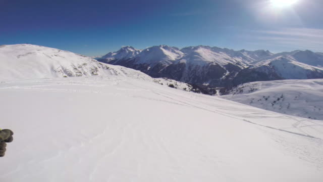 pov of a man skiing in the mountains in fresh powder snow. - bastoncino da sci video stock e b–roll